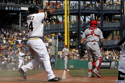Pittsburgh Pirates' Pedro Alvarez (24) points to teammate Tony Sanchez on second base after scoring on a Sanchez double off St. Louis Cardinals starting pitcher Adam Wainwright during the seventh inning of a baseball game in Pittsburgh, Sunday, April 6, 2014. The Pirates won 2-1. (AP Photo/Gene J. Puskar)