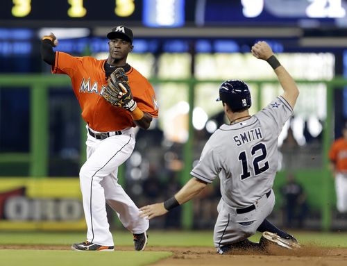 San Diego Padres' Seth Smith (12) is forced out at second base by Miami Marlins shortstop Adeiny Hechavarria in the third inning of a baseball game in Miami, Sunday, April 6, 2014. Chase Headley was safe at first base on a fielder's choice. (AP Photo/Alan Diaz)