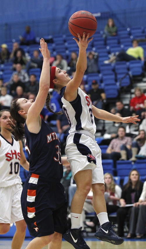 "Al Hartmann  |  The Salt Lake Tribune Springville School's 5'2"" guard Savannah Park slides past Mtn. Crest High School's Kenzie Rasmussen for a layup during a Girl's 4A play off game at Salt Lake Community College Tuesday, February 19."