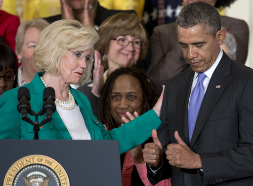 President Barack Obama gives two thumbs as Women's rights activist Lilly Ledbetter, left, acknowledges him in the East Room of the White House in Washington, Tuesday, April 8, 2014, during an event marking Equal Pay Day, and where the president will announce and sign new executive actions to strengthen enforcement of equal pay laws for women. The president and his Democratic allies in Congress are making a concerted election-year push to draw attention to women's wages, linking Obama executive actions with pending Senate legislation aimed at closing a compensation gendergap that favors men. (AP Photo/Carolyn Kaster)