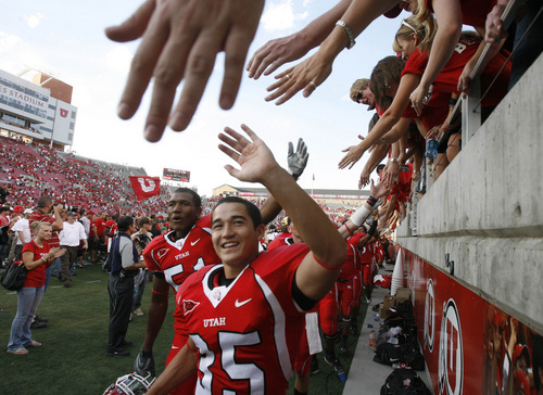 Rick Egan  |  Tribune file photo  Kicker Louie Sakoda high-fives fans after Utah beat UCLA  44-6 at Rice-Eccles Stadium in 2007.
