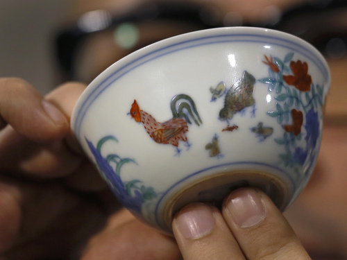 """The Meiyintang """"Chicken Cup"""" from the Chinese Ming Dynasty (1368-1644) is displayed during a press conference in Hong Kong, Tuesday, April 8, 2014. Sotheby's said Shanghai collector Liu Yiqian won the bidding for the """"Chicken Cup,"""" which is decorated with a rooster, hen and their chicks. Including the auction house's commission, the price for the small cup comes to HK$281.2 million (US$36.1 million), which Sotheby's said is a world record price for Chinese porcelain. (AP Photo/Vincent Yu)"""