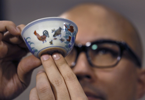 """Sotheby's Deputy Chairman for Asia Nicholas Chow presents the Meiyintang """"Chicken Cup"""" from the Chinese Ming Dynasty (1368-1644) during a press conference in Hong Kong, Tuesday, April 8, 2014. Sotheby's said Shanghai collector Liu Yiqian won the bidding for the """"Chicken Cup,"""" which is decorated with a rooster, hen and their chicks. Including the auction house's commission, the price for the small cup comes to HK$281.2 million (US$36.1 million), which Sotheby's said is a world record price for Chinese porcelain. (AP Photo/Vincent Yu)"""