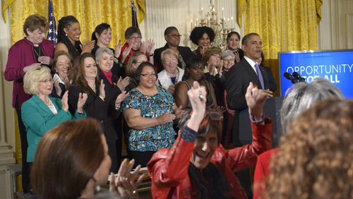 Rep. Rosa DeLauro, D-Conn., center, cheers as President Barack Obama speaks in the East Room of the White House in Washington, Tuesday, April 8, 2014, during an event marking Equal Pay Day. Obama announced new executive actions to strengthen enforcement of equal pay laws for women. The president and his Democratic allies in Congress are making a concerted election-year push to draw attention to women's wages. Lilly Ledbetter, in green, watches at left. (AP Photo/Susan Walsh)