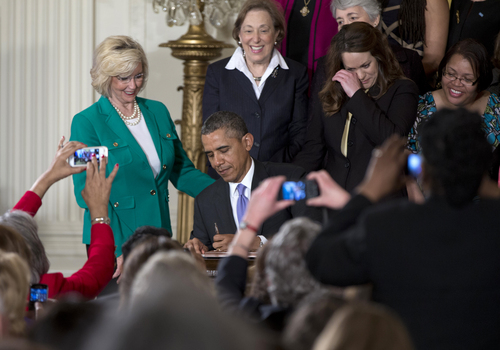Women's rights activist Lilly Ledbetter watches at left, and members of the audience take photos, as President Barack Obama signs new executive actions to strengthen enforcement of equal pay laws for women, Tuesday, April 8, 2014, in the East Room of the White House in Washington. The event marked Equal Pay Day. The president and his Democratic allies in Congress are making a concerted election-year push to draw attention to women's wages, linking Obama executive actions with pending Senate legislation aimed at closing a compensation gender gap that favors men. (AP Photo/Carolyn Kaster)