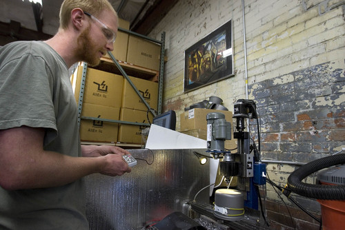 Paul Fraughton  |   Salt Lake Tribune Paul Slusser, runs a  computer assisted drilling machine to drill out a Powerpot before the installation of the metal plate and  components that allows the pot  to produce electricity.                      Tuesday, May 28, 2013