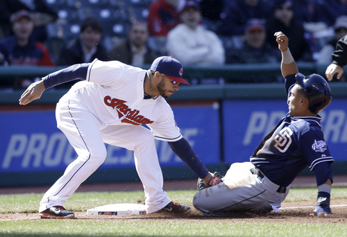 San Diego Padres' Everth Cabrera, right, is caught stealing third base as Cleveland Indians' Mike Aviles makes the tag in the third inning in the second game of a baseball doubleheader on Wednesday, April 9, 2014, in Cleveland. (AP Photo/Tony Dejak)