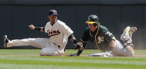 Oakland Athletics' Josh Donaldson, right, goes into second base with a double as Minnesota Twins shortstop Pedro Florimon, left, attempts the tag during the fifth inning of a baseball game, Wednesday, April 9, 2014 in Minneapolis. (AP Photo/Tom Olmscheid)