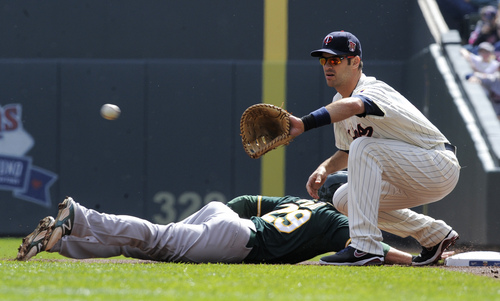Oakland Athletics' Sam Fuld, left, dives back to first base as Minnesota Twins' Joe Mauer, right, takes the throw during the first inning of a baseball game, Wednesday, April 9, 2014 in Minneapolis. (AP Photo/Tom Olmscheid)