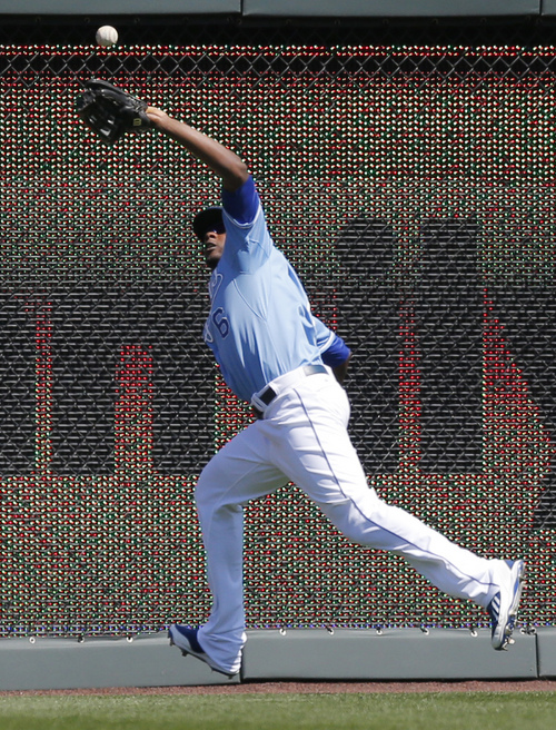 Kansas City Royals center fielder Lorenzo Cain catches a fly ball hit by Tampa Bay Rays' David DeJesus during the first inning of a baseball game at Kauffman Stadium in Kansas City, Mo., Wednesday, April 9, 2014. (AP Photo/Orlin Wagner)