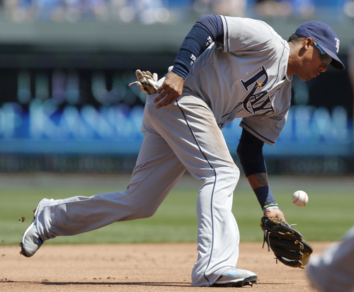 Tampa Bay Rays shortstop Yunel Escobar fields a ball hit by Kansas City Royals' Johnny Giavotella during the first inning of a baseball game at Kauffman Stadium in Kansas City, Mo., Wednesday, April 9, 2014. Giavotella was out at first base on the play. (AP Photo/Orlin Wagner)