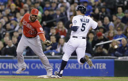 Seattle Mariners' Brad Miller (5) is safe at first as the ball goes past Los Angeles Angels first baseman Ian Stewart on a throwing error by second baseman Howie Kendrick in the sixth inning of a baseball game Wednesday, April 9, 2014, in Seattle. (AP Photo/Elaine Thompson)
