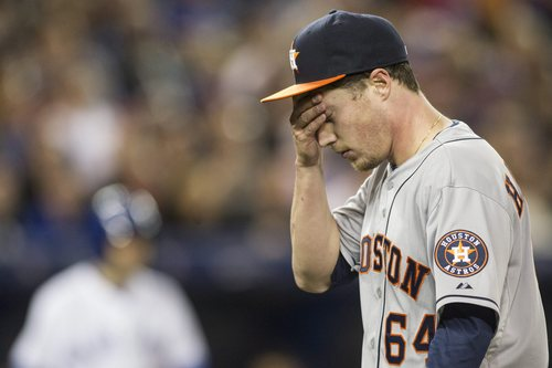 Houston Astros starting pitcher Lucas Harrell returns to the dugout after the third inning of a baseball game against the Toronto Blue Jays on Wednesday, April 9, 2014, in Toronto. (AP Photo/The Canadian Press, Chris Young)