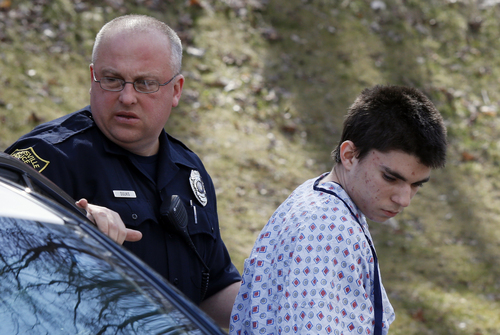 Alex Hribal, the suspect in the multiple stabbings at the Franklin Regional High School in Murrysville, Pa., is escorted by police to a district magistrate to be arraigned on Wednesday, April 9, 2014, in Export, Pa. Authorities say Hribal has been charged after allegedly stabbing and slashing at least 19 people, including students, in the crowded halls of his suburban Pittsburgh high school Wednesday. (AP Photo/Keith Srakocic)