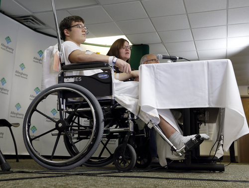 Brett Hurt, 16, a sophomore at Franklin Regional High School in Murrysville, Pa.,and a victim in the stabbings that took place their on April 9, sits in a wheelchair next to his mother Amanda Leonard during a news conference at Forbes Regional Hospital, Thursday, April 10, 2014, in Monroeville, Pa. Authorities have charged Alex Hribal, 16, with four counts of attempted homicide and 21 counts of aggravated assault in the attack. (AP Photo/Keith Srakocic)