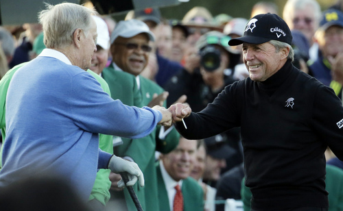 Gary Player, right, touches fists with Jack Nicklaus after hitting a ceremonial drive on the first tee during the first round of the Masters golf tournament Thursday, April 10, 2014, in Augusta, Ga. (AP Photo/Charlie Riedel)