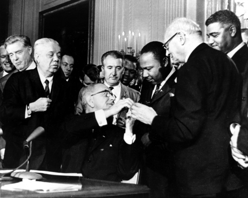 FILE 0 In this July 2, 1964, file photo, President Lyndon B. Johnson reaches to shake hands with Dr. Martin Luther King Jr. after presenting the civil rights leader with one of the 72 pens used to sign the Civil Rights Act in Washington. Surrounding the president, from left, are, Rep. Roland Libonati, D-Ill., Rep. Peter Rodino, D-N.J., Rev. King, Emanuel Celler, D-N.Y., and behind Celler is Whitney Young, executive director of the National Urban League. President Barack Obama was 2-years-old when Johnson signed the Civil Rights Act. Half a century later, the first black president will commemorate what's been accomplished in his lifetime. He'll also recommit the nation to fighting deep inequalities that remain.  (AP Photo)