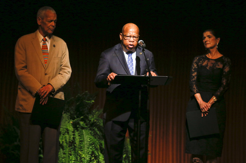 U.S. Rep. John Lewis, of Georgia, center, gives a reading during the Civil Rights Summit on Wednesday, April 9, 2014, in Austin, Texas. Former NAACP chairman Julian Bond, left, and Luci Baines Johnson, right, daughter of former President Lyndon Baines Johnson, also spoke. (AP Photo/Jack Plunkett)