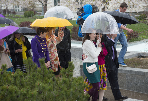 Steve Griffin  |  The Salt Lake Tribune   Members and supporters of the Ordain Women, led by Hannah Wheelwright and Kate Kelly, right, brave a hail storm as they walk to the Tabernacle on Temple Square to seek standby tickets to the all-male general priesthood meeting in Salt Lake City, Utah Saturday, April 5, 2014.