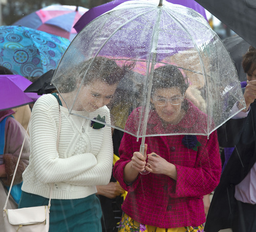 Steve Griffin  |  The Salt Lake Tribune   Hannah Wheelwright and Kate Kelly, of the group Ordain Women, brave a hail storm as they walk with supporters and other members to the Tabernacle on Temple Square to seek standby tickets to the all-male general priesthood meeting in Salt Lake City, Utah Saturday, April 5, 2014.