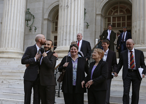 Plaintiffs and gay rights activists Derek Kitchen, left, and his partner Moudi Sbeity embrace as they leave court with other gay rights supporters after a hearing at the U.S. Circuit Court of Appeals in Denver, Thursday, April 10, 2014. The court is to decide if it agrees with a federal judge in Utah who in mid-December overturned a 2004 voter-passed gay marriage ban, saying it violates gay and lesbian couples' rights to due process and equal protection under the 14th Amendment. (AP Photo/Brennan Linsley)
