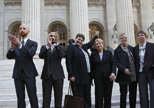 Plaintiffs challenging Utah's gay marriage ban, from left, Derek Kitchen, his partner Moudi Sbeity, Kate Call, her partner Karen Archer, Laurie Wood and her partner Kody Partridge stand together after leaving court following a hearing at the U.S. Circuit Court of Appeals in Denver, Thursday, April 10, 2014. The court is to decide if it agrees with a federal judge in Utah who in mid-December overturned a 2004 voter-passed gay marriage ban, saying it violates gay and lesbian couples' rights to due process and equal protection under the 14th Amendment. (AP Photo/Brennan Linsley)