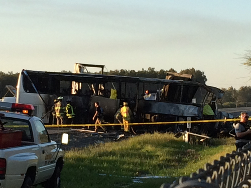 In this photo provided by Andrew Hutchens, authorities work the scene where nine people were killed in a three-vehicle crash involving a bus carrying high school students on a visit to a college, Thursday, April 10, 2014, near Orland, Calif. Authorities said it is not yet clear what caused the crash but that it involved a tour bus, a FedEx truck and a Nissan Altima. (AP Photo/Andrew Hutchens)