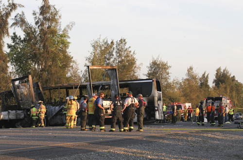 Rescue workers, police and firefighters work the scene where nine people were killed in a three-vehicle crash involving a bus carrying high school students on a visit to a college, Thursday, April 10, 2014, near Orland, Calif. Authorities said it is not yet clear what caused the crash but that it involved a tour bus, a FedEx truck and a Nissan Altima. (AP Photo/The Record Searchlight, Greg Barnette)
