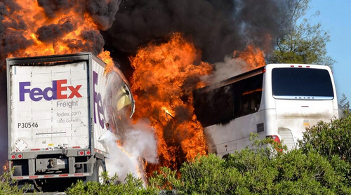 Massive flames engulf a tractor-trailer and a tour bus just after they collide on Interstate 5, Thursday April, 10, 2014, near Orland, Calif. At least 10 people were killed in the crash, authorities said. (AP Photo/Jeremy Lockett)