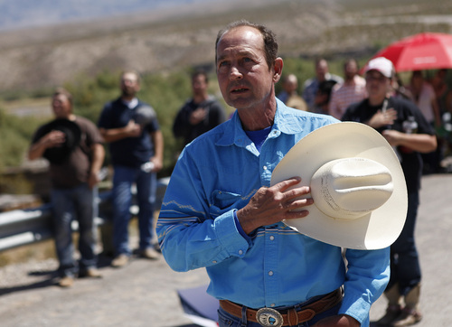 """Chris Miller holds his hand over his heart during a rally in support of Cliven Bundy near Bunkerville Nev. Monday, April 7, 2014, 2014. The Bureau of Land Management has begun to round up what they call """"trespass cattle"""" that rancher Cliven Bundy has been grazing in the Gold Butte area 80 miles northeast of Las Vegas. (AP Photo/Las Vegas Review-Journal, John Locher)"""
