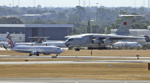 A Chinese  Ilyushin IL-76 aircraft, right, lands at Perth International Airport after returning from the ongoing search operations for missing Malaysia Airlines Flight 370 in Perth, Australia, Sunday, April 13, 2014. Following four strong underwater signals in the past week, all has gone quiet in the hunt for the missing Malaysian airline, meaning the batteries on the all-important black boxes may have finally died. Despite having no new pings to go on, crews are continuing their search Sunday for debris and any sounds that could still be emanating. (AP Photo/Rob Griffith)