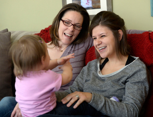 "Al Hartmann  |  The Salt Lake Tribune  Kimberly, left, and Amber Leary play ""Itsy-Bitsy Spider"" with their 15-month-old daughter on Thursday, February 27, at their home. They are among an unknown number of gay couples in Utah whose efforts to pursue second-parent adoptions have been thwarted by a stay of a court decision overturning the same-sex marriage ban and intervention by the Utah Attorney General's Office."