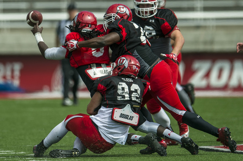 Chris Detrick  |  The Salt Lake Tribune Utah Utes quarterback Brandon Cox (5) is sacked by Utah Utes defensive end Hayden Clegg (92) and Utah Utes Nick Mitchell (78) during a scrimmage at Rice-Eccles Stadium DOW} April 12, 2014.