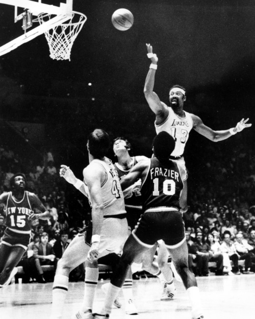 The Los Angeles Lakers' Wilt Chamberlain (13) fires a leaping scoop shot against the New York Knicks in their NBA finals play-off game at Los Angeles, Ca. on April 30, 1972.  Teammate Jerry West (4) is at left.  The Knicks players are Earl Monore (15), Walt Frazier (10), and Jerry Lucas, center.  (AP Photo)