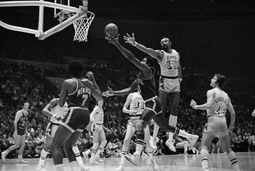 Los Angeles Lakers' Wilt Chamberlain (13) stretches to try to block shot by New York Knicks Willis Reed, but Reed got past Wilt's long arm and scored during the second game of NBA championship playoff series in Inglewood, Calif., Thursday, May 4, 1973. Left is Knicks Dean Meminger (7). Knicks defeated Lakers 99-95, to even series at a game apiece. (AP Photo