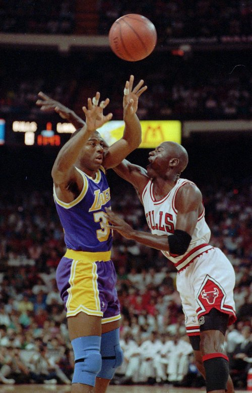 """Chicago Bulls' Michael Jordan tries to block Los Angeles Lakers' Earvin """"Magic"""" Johnson during the NBA Finals in Chicago June 3, 1991. Johnson, driven from basketball nearly five years ago when he learned he had the AIDS virus, returned to the NBAfrom an off-and-on retirement. (AP Photo/File)"""