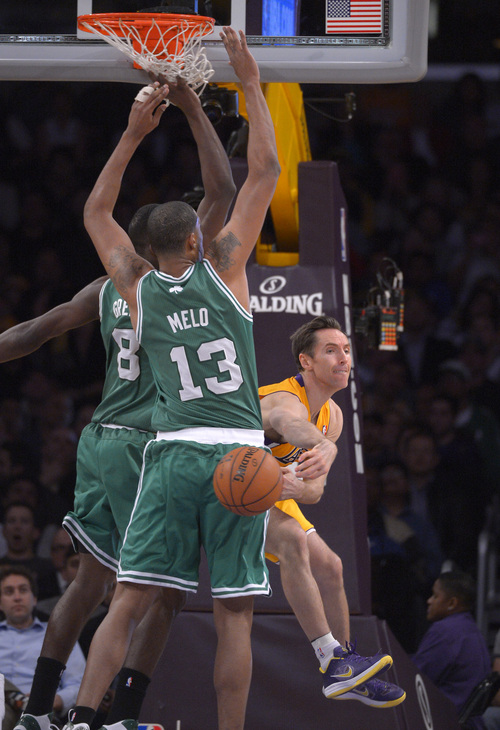 Los Angeles Lakers guard Steve Nash, right, passes the ball by Boston Celtics forward Jeff Green, left, and center Fab Melo, of Brazil, during the second half of their basketball game, Wednesday, Feb. 20, 2013, in Los Angeles. Nash had seven assists, giving him 10,144 while passing Magic Johnson for sole possession of fourth place on the career list. The Lakers won 113-99. (AP Photo/Mark J. Terrill)