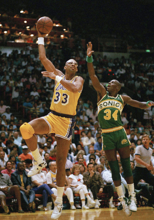 FILE - In this April 24, 1989, file photo, Los Angeles Lakers' Kareem Abdul-Jabbar goes up on a sky hook against Seattle Sonics' Xavier McDaniel during an NBA game in Inglewood, Calif. Abdul-Jabbar is being treated for a rare form of leukemia, and the basketball great said that his prognosis is encouraging. (AP Photo/Reed Saxon, File)