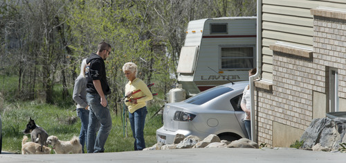 Steve Griffin     The Salt Lake Tribune  Sandee Wall, a next door neighbor, center, talks with a man and women at the house where seven dead infants were found April 13, 2014 in this Pleasant Grove, Utah home. Police believe Megan Huntsman, 39, gave birth to the babies then killed them over the past decade. The home was photographed Monday April, 14, 2014.