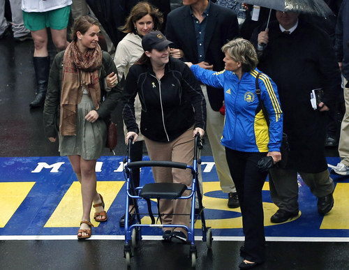 2013 Boston Marathon bombing survivor Erika Brannock, a pre-school teacher from the Baltimore area, and her mother, Carol Downing, at right, walk across the Marathon finish line after a remembrance ceremony on Boylston Street in Boston, Tuesday, April 15, 2014. (AP Photo/Elise Amendola)
