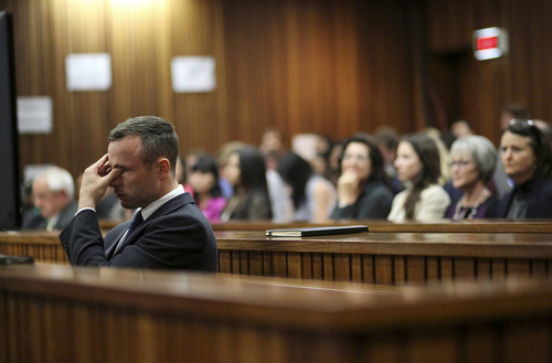 Oscar Pistorius rubs his eye in court in Pretoria, South Africa, Tuesday, April 15, 2014, after earlier questioning by state prosecutor Gerrie Nel.  Pistorius is charged with the murder of his girlfriend Reeva Steenkamp. (AP Photo/Siphiwe Sibeko, Pool)