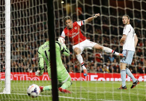 Arsenal's Olivier Giroud, center, scores a goal past West Ham's goalkeeper Adrian, left, during the English Premier League soccer match between Arsenal and West Ham United at the Emirates stadium in London, Tuesday, April 15, 2014. (AP Photo/Kirsty Wigglesworth)