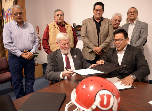 Al Hartmann  |  The Salt Lake Tribune David W. Pershing, University of Utah president, front left, and Gordon Howell, chairman of the Ute Indian Tribe Business Committee sign a memorandum of understanding outlining the University's continued use of the Ute name for its athletics teams.  Members of the Ute Business Committe in rear watch the signing at a ceremony at Fort Duchesne Tuesday April 15.