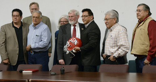 Al Hartmann  |  The Salt Lake Tribune David W. Pershing, University of Utah president, center, and Gordon Howell, chairman of the Ute Indian Tribe Business Committee pose for a photo with a Ute football helmet with members of the business committee and univeristy officials after signing a memorandum of understanding outlining the University's continued use of the Ute name for its athletics teams at a ceremony at Fort Duchesne Tuesday April 15.