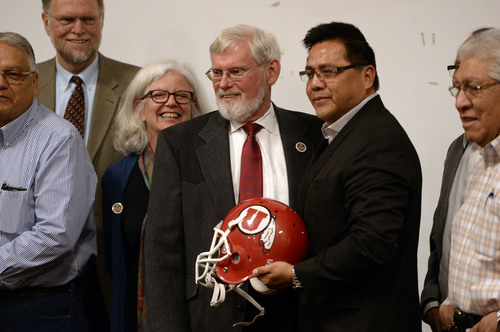 Al Hartmann  |  The Salt Lake Tribune David W. Pershing, University of Utah president, center and Gordon Howell, chairman of the Ute Indian Tribe Business Committee pose for a photo with a Ute football helmet after signing a memorandum of understanding outlining the University's continued use of the Ute name for its athletics teams at a ceremony at Fort Duchesne Tuesday April 15.