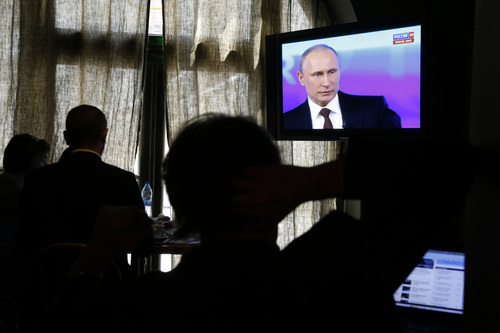 "Reporters listen to Russian President Vladimir Putin's speech, displayed on TV screens during a nationally televised question-and-answer session in Moscow, Thursday, April 17, 2014. Russia's President Vladimir Putin on Thursday dismissed claims that Russian special forces are fomenting unrest in eastern Ukraine as ""nonsense,"" but expressed hope for success of four-way talks on settling the crisis. (AP Photo/Pavel Golovkin)"