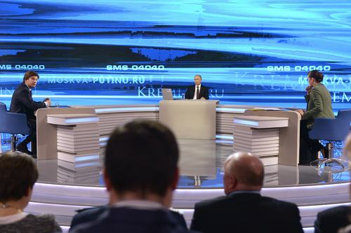 "Russian President Vladimir Putin, background center, listens during a nationally televised question-and-answer session in Moscow on Thursday, April 17, 2014. Russia's President Vladimir Putin on Thursday dismissed claims that Russian special forces are fomenting unrest in eastern Ukraine as ""nonsense,"" but voiced hope for success of four-way talks on settling the crisis. (AP Photo/RIA Novosti, Alexei Nikolsky, Presidential Press Service)"
