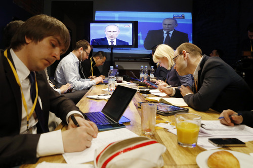 Reporters listen to Russian President Vladimir Putin's speech, displayed on TV screens during a nationally televised question-and-answer session in Moscow, Thursday, April 17, 2014.  (AP Photo/Pavel Golovkin)