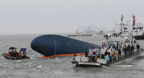 South Korean Coast Guard officers search for missing passengers aboard a sunken ferry in the water off the southern coast near Jindo, South Korea, Thursday, April 17, 2014.  Strong currents, rain and bad visibility hampered an increasingly anxious search Thursday for more than 280 passengers still missing a day after their ferry flipped onto its side and sank in cold waters off the southern coast of South Korea. (AP Photo/Ahn Young-joon)