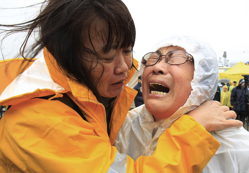 Relatives of a passenger aboard a sunken ferry weep as they wait for news on the rescue operation, at a port in Jindo, South Korea, Thursday, April 17, 2014.  Strong currents, rain and bad visibility hampered an increasingly anxious search Thursday for more than 280 passengers still missing a day after their ferry flipped onto its side and sank in cold waters off the southern coast of South Korea. (AP Photo/Ahn Young-joon)